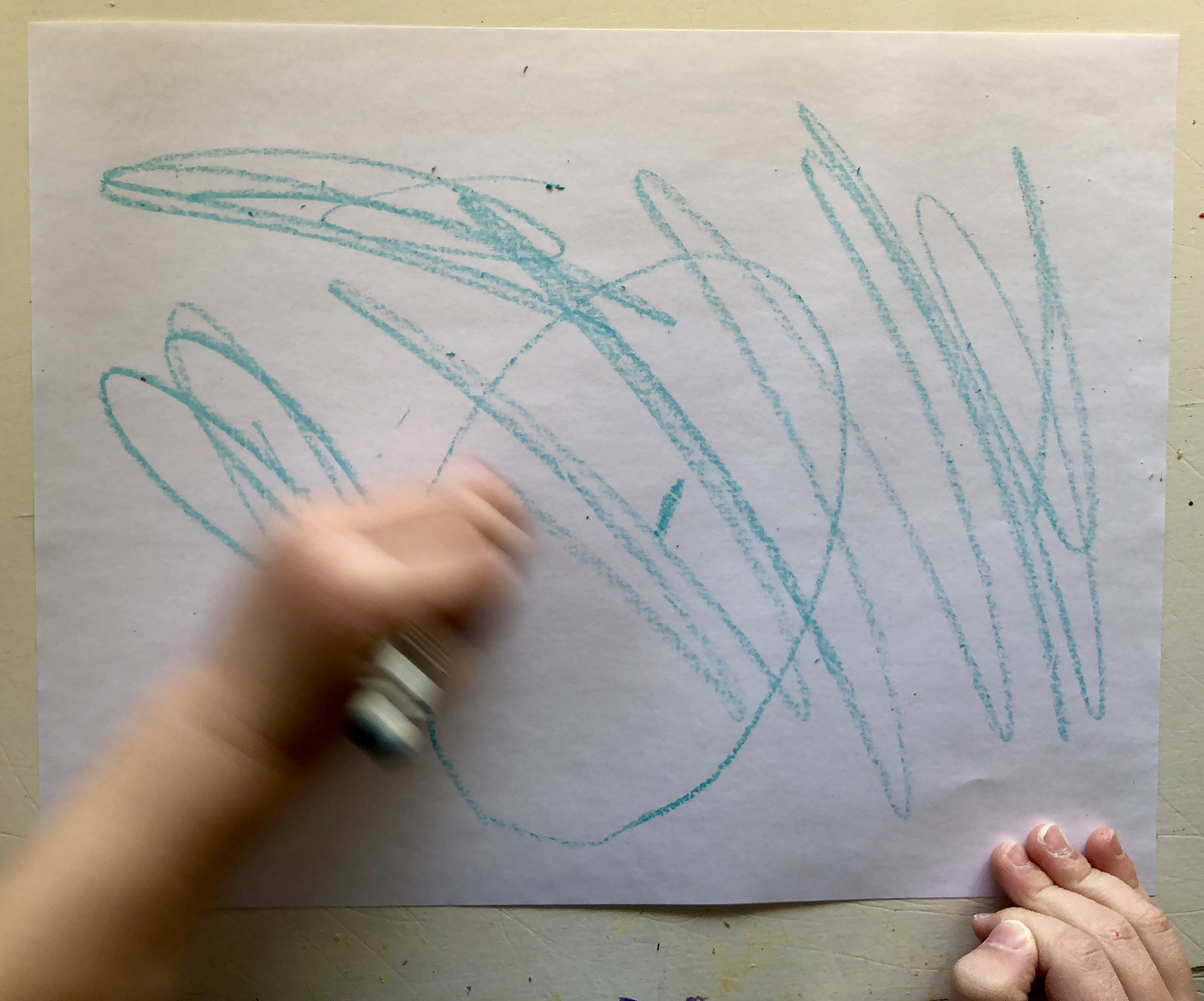 child's hand scribbling with a crayon