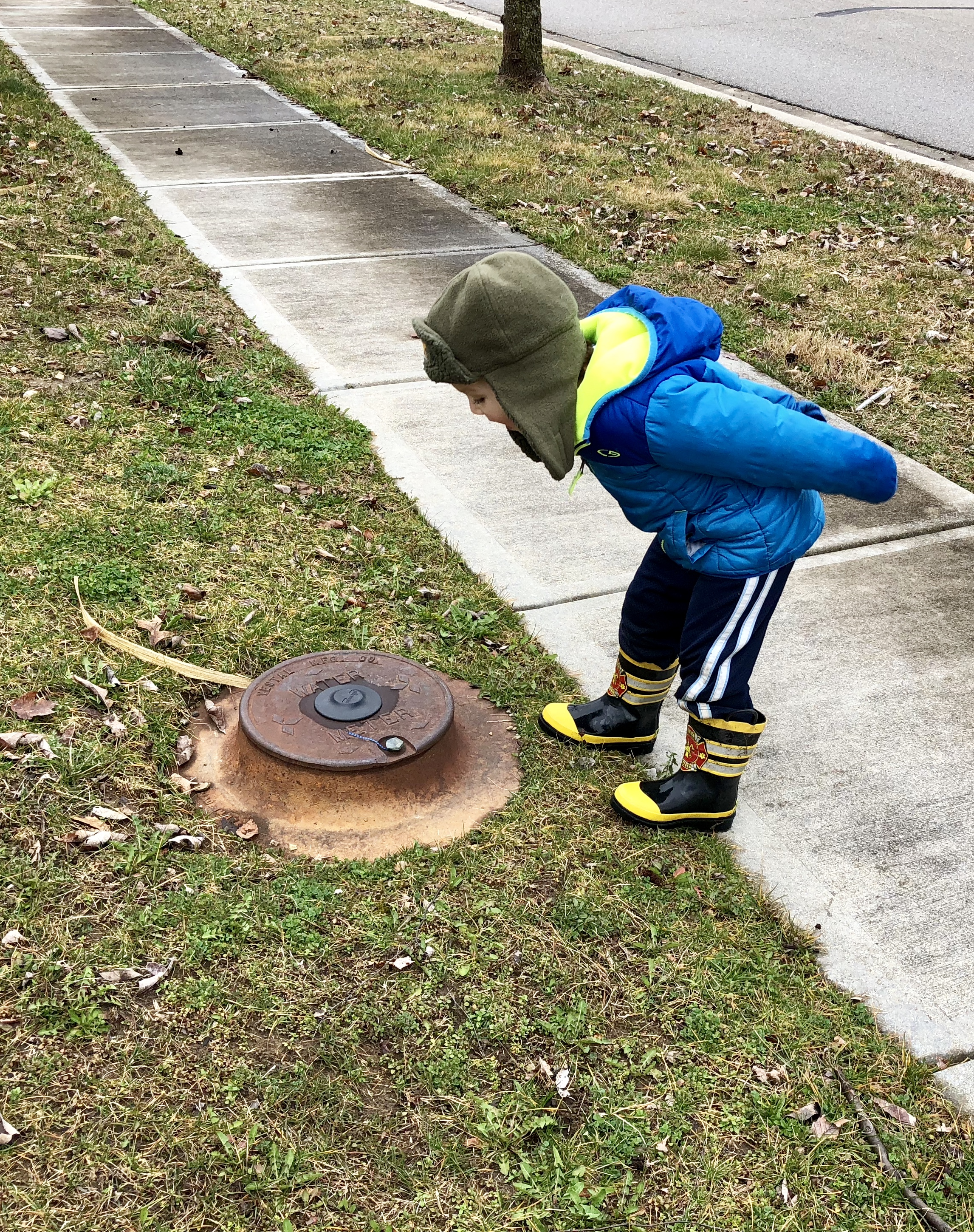 boy leaning over a water access cover and calling out