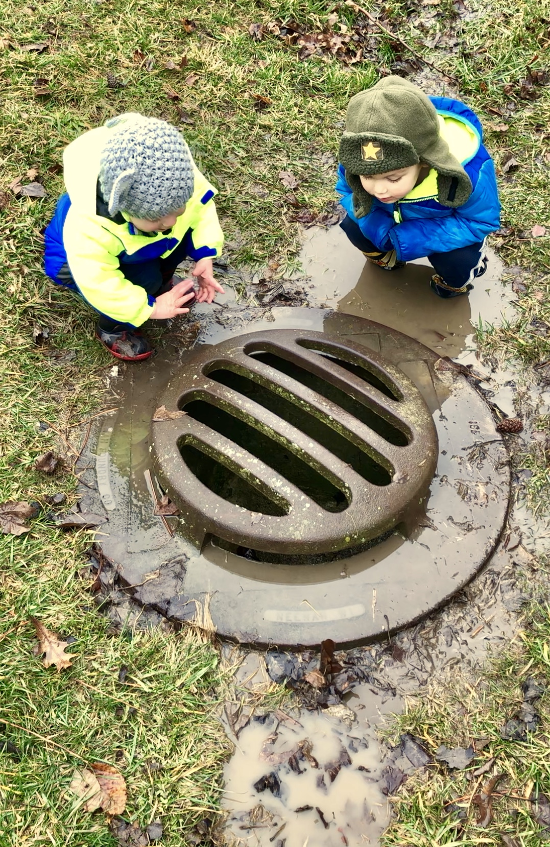 2 boys leaning over a drain