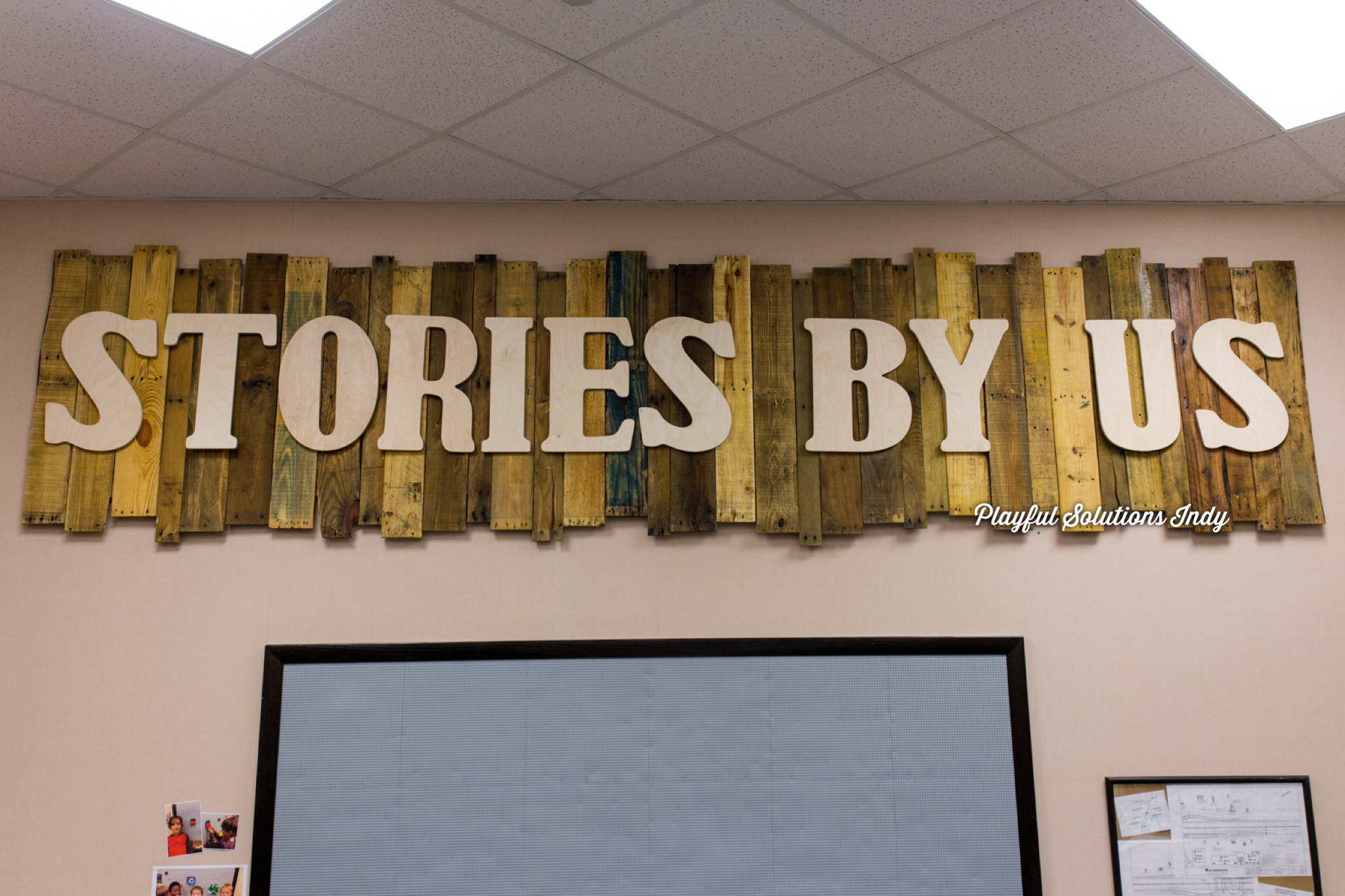 wooden sign with unfinished letters that spell out stories by us