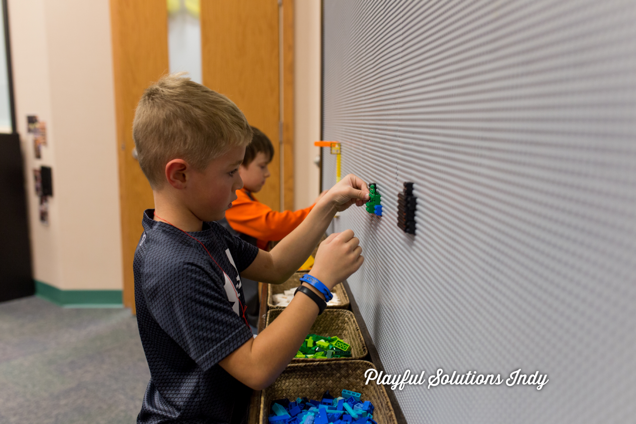 Boys building on a Lego wall